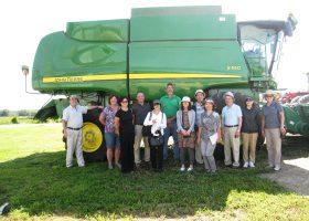 「GM栽培に変えてから同じ面積で2倍の収穫が得られるようになった」と語るマーク・スコットさん(後列中央)一家と視察団。後ろは収穫用の大型トラクター。ミズーリ州ウェンツビルで。