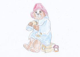 マーマレードサンドイッチを頬張るパディントン。赤い帽子と青いダッフルコート、マーマレードの入った皮トランクがトレードマークである